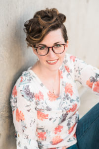 Charlie Holmberg Headshot by Alyssa Tsuchiya Photography. A woman in a white blouse with pink flowers, with a dark-colored pixie cut and round glasses.