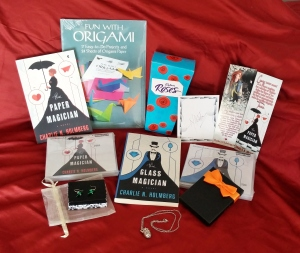 $50 Amazon gift card, signed paperback copies of The Paper Magician and The Glass Magician, signed audiobook copies of The Paper Magician and The Glass Magician, signed bookplate, bookmark, origami kit, Cadbury roses, paper crane earrings, and an atomically correct silver heart necklace.